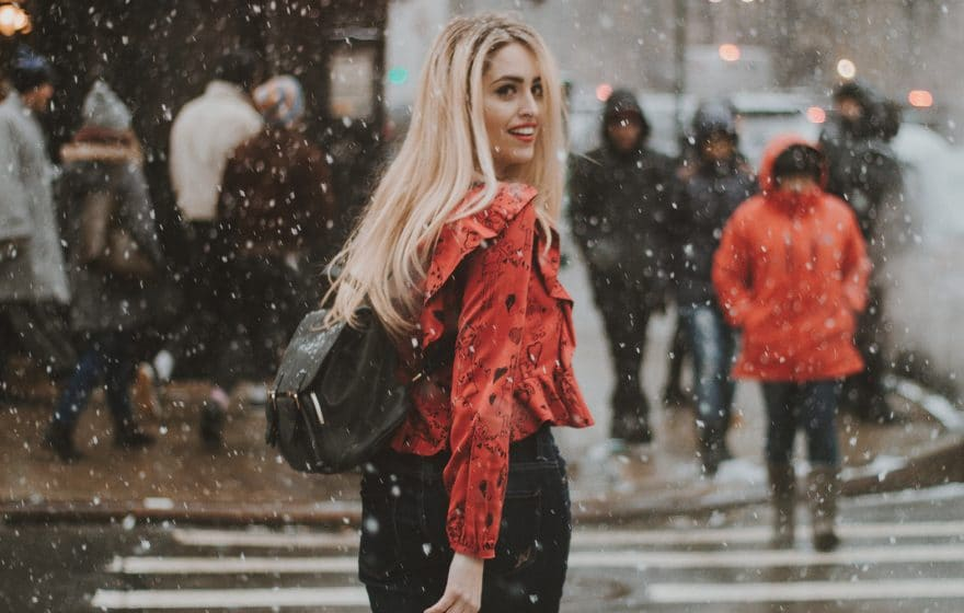girl walking in the street while snowing