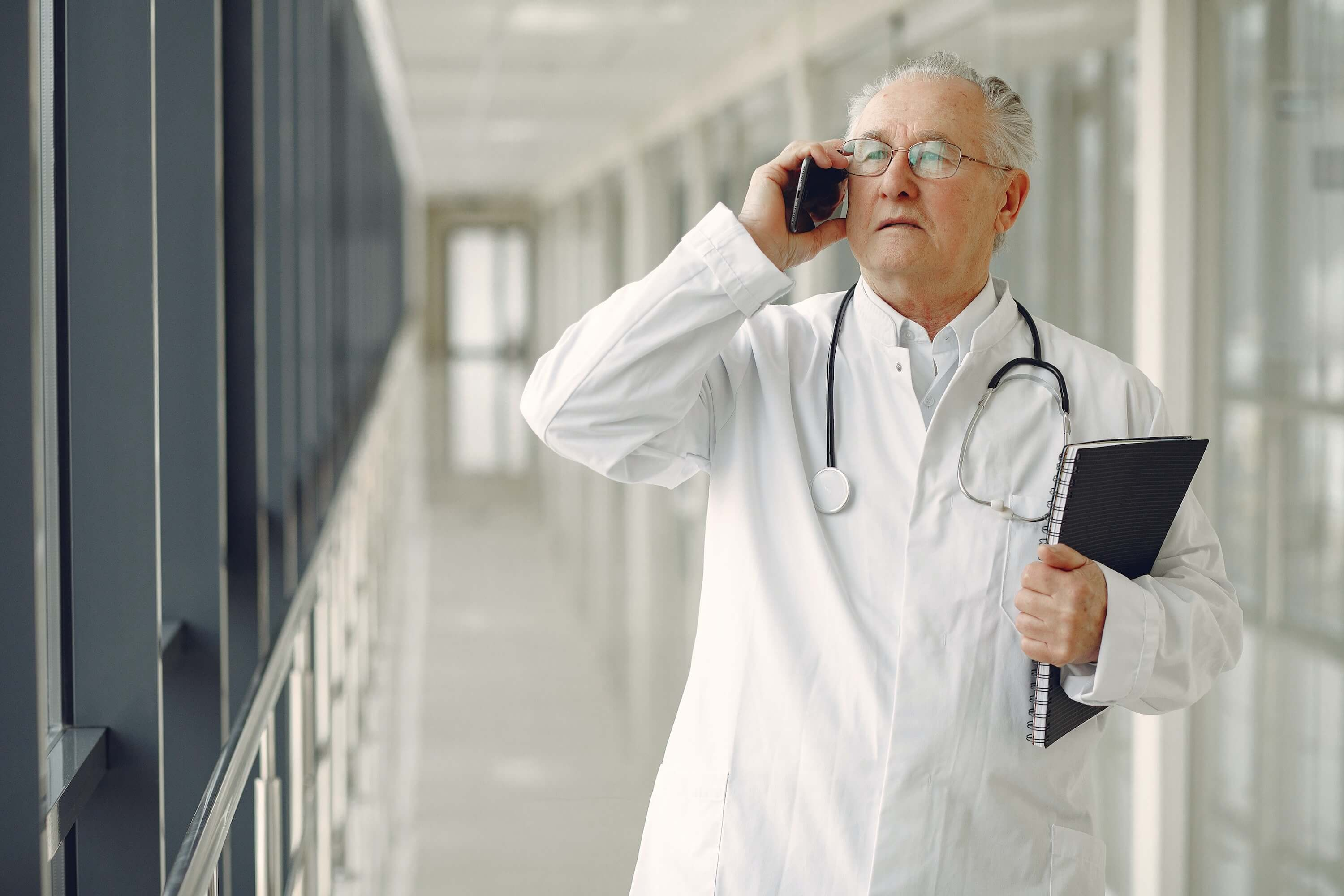 doctor in medical uniform talking on mobile phone in clinic