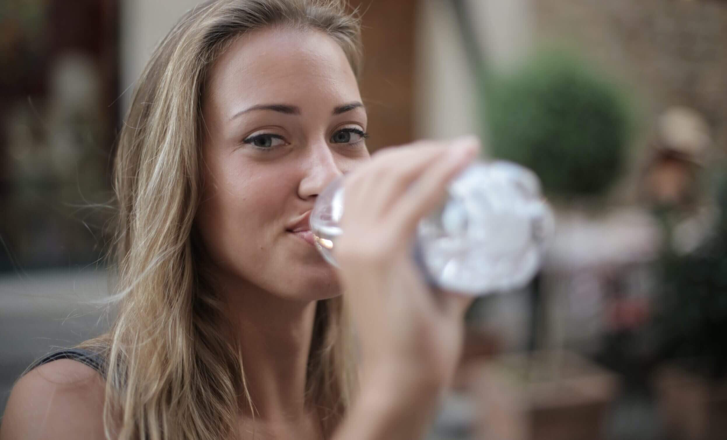 smiling-woman-drinking-water-from-a-plastic-bottle