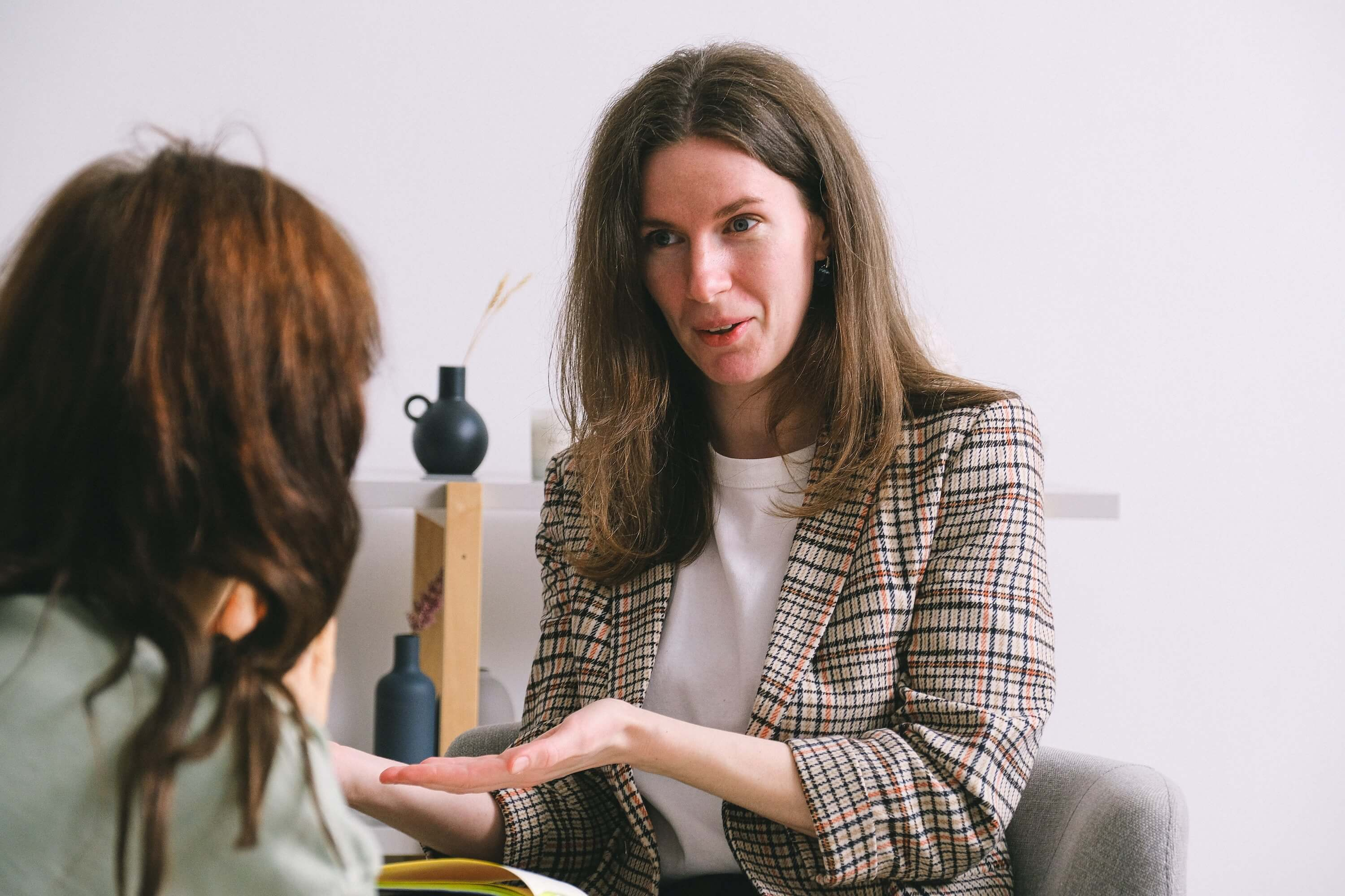smiling-therapist-speaking-with-anonymous-female-patient-in-light-office