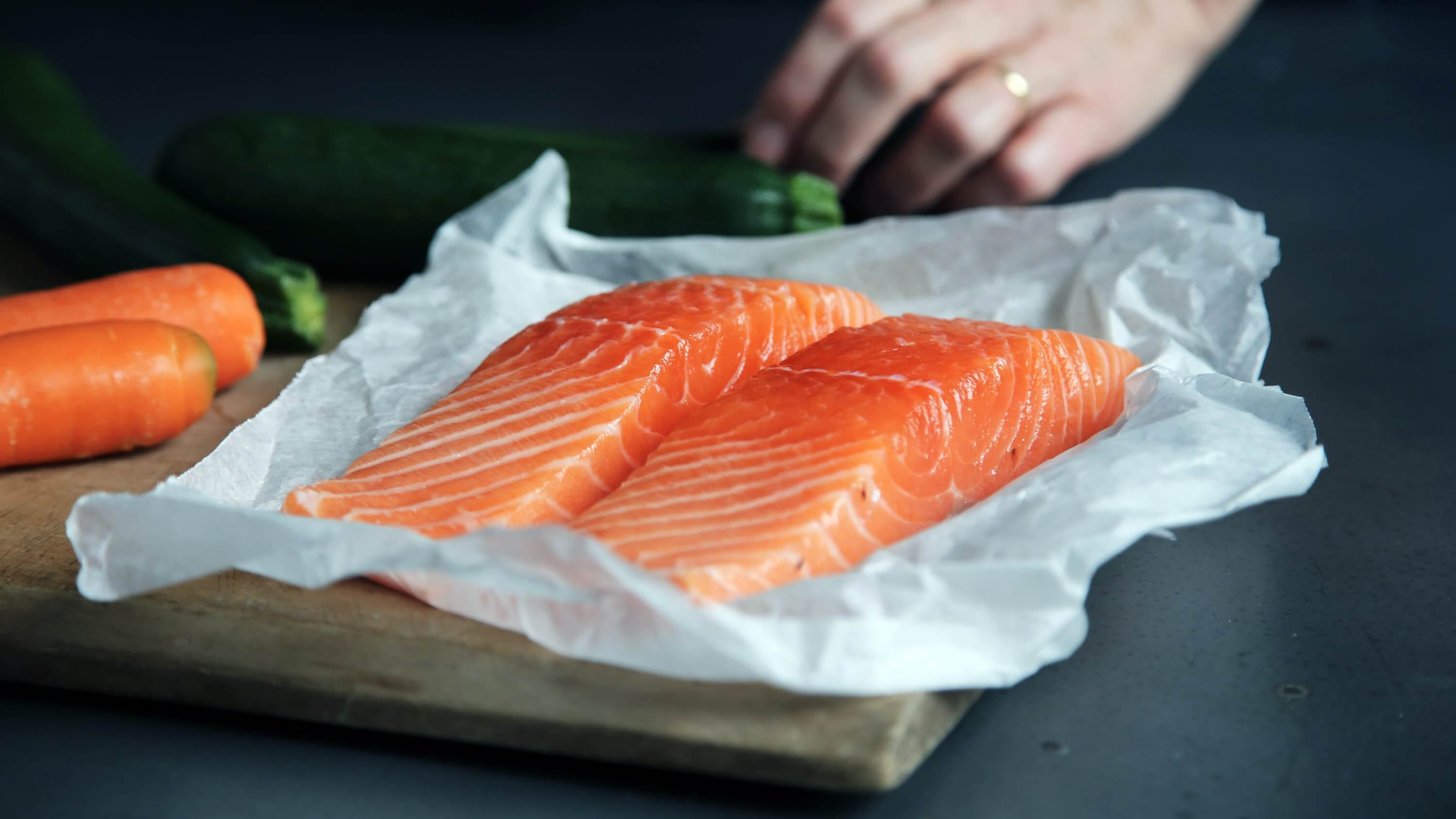 raw salmon fillets on a chopping board